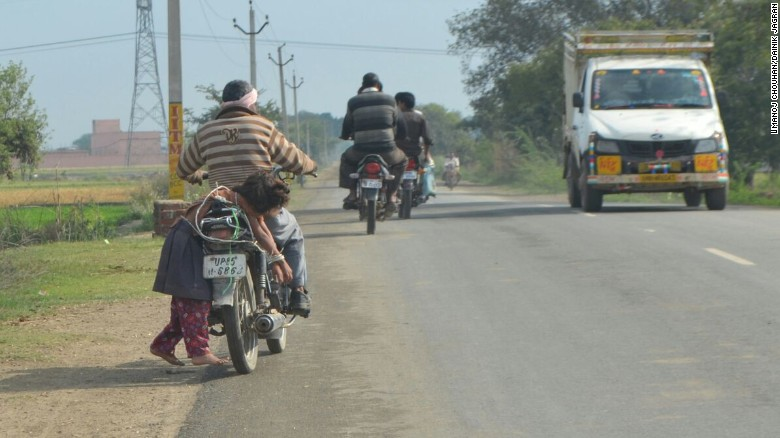 Girl seen bound to fathers motorbike.